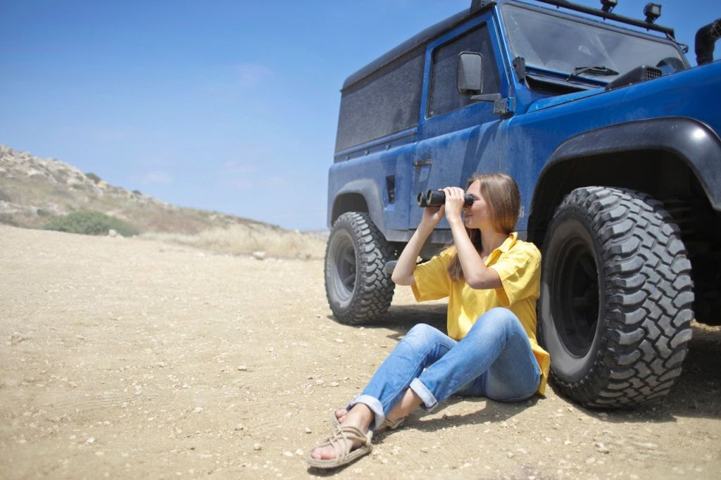 Parenting and Lifestyle blog LifeByVal. Image: Woman sitting near wheel of jeep with binoculars.