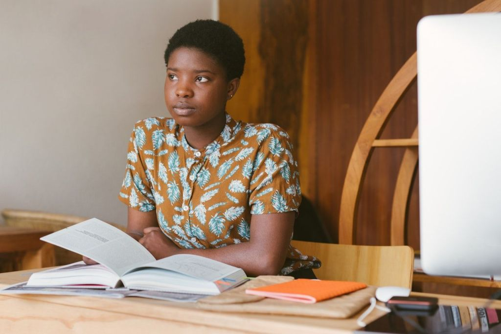 Parenting and lifestyle blog LifeByVal. Image: Black woman sitting at desk with book opened.